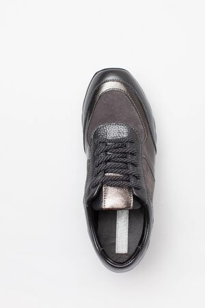 Grey female sneaker with sequins on white background. Top view. Flatley. Copy space text.