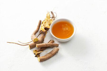 La raíz cruda de la planta y la miel de Rumex crispus (muelle amarillo) se utiliza para tratar los resfriados y los procesos inflamatorios en la medicina popular. Foto de archivo