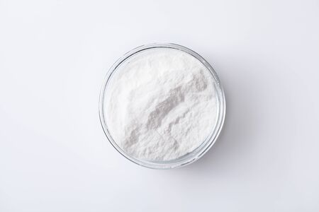 Baking soda in a jar and bowl on a white glossy background. The use of soda in cosmetics, everyday life and folk medicine. Copyspace text Stock Photo