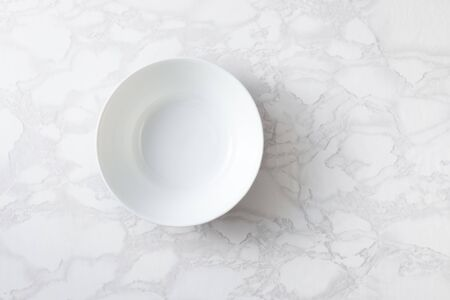 An empty white bowl on a marble surface. Top view. Space for text.