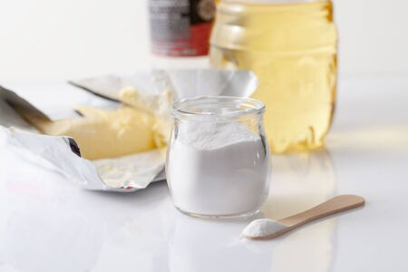 Stabilizer in the form of powder in a jar with oil in a bottle and a pack of butter. The stabilizer is used in fatty foods and is harmful to health. Copyspace text