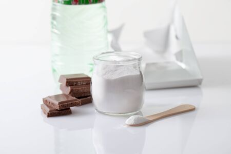 Stabilizer in the form of powder in a jar with a carbonated drink in a bottle and pieces of chocolate. Stabilizer and sweetener aspartame is used in sweet foods and is harmful to health Stock Photo