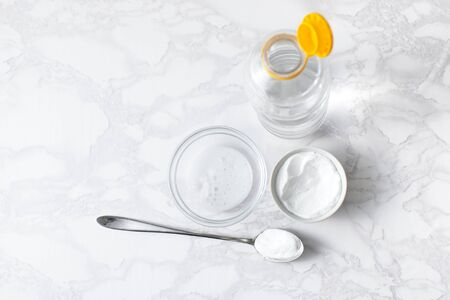 Reaction of baking soda with vinegar in a bowl with a Cup of dry soda, a spoon and a bottle of vinegar. Copyspace text