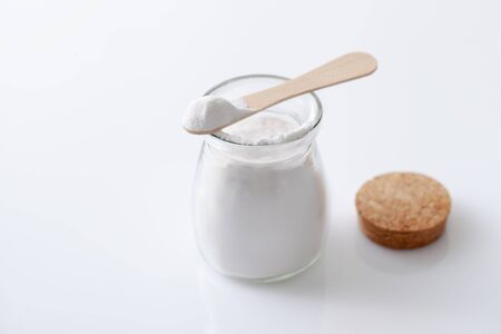 Baking soda in a jar and bowl on a white glossy background. The use of soda in cosmetics, everyday life and folk medicine. Copyspace text