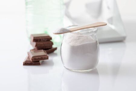 Stabilizer in the form of powder in a jar with a carbonated drink in a bottle and pieces of chocolate. Stabilizer and sweetener aspartame is used in sweet foods and is harmful to health Archivio Fotografico