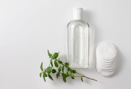Micellar cleansing water and discs to remove cosmetics and cleanse the skin on grey. Copy space text
