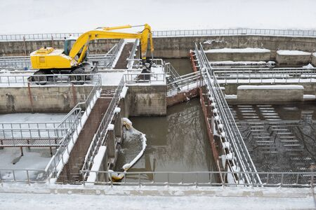 Snow plow excavator clears snow at the water utility in the spring