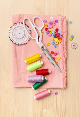 Sewing supplies on wooden table: sewing thread, spool of thread, pieces of cloth, needles, buttons.