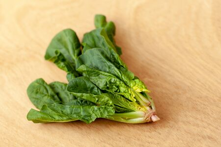 Fresh spinach: marsh grass, patience dock leaves on a wooden background 版權商用圖片