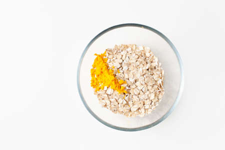 Bright yellow turmeric powder in a bowl of oatmeal on a white background for making a face mask. Copy space text.