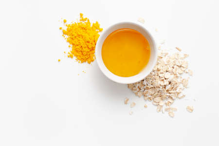 Ingredients recipe homemade face mask made of turmeric, honey and oatmeal on a white background. Copy space text.