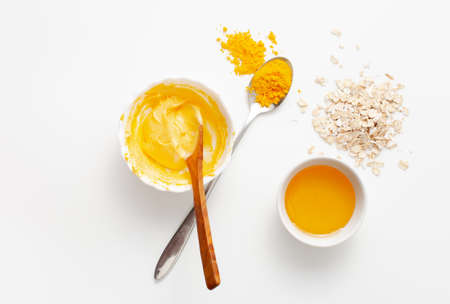 Recipe homemade face mask of turmeric, honey and oatmeal mixed in a bowl on a white background. Copy space text.
