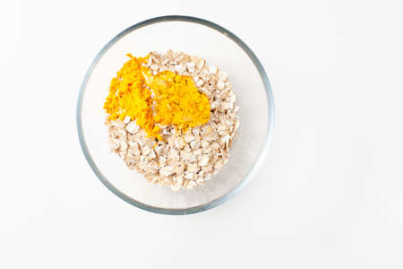 Bright yellow aromatic spice turmeric in a bowl with oatmeal and honey on a white background for making a face mask. Copy space text.