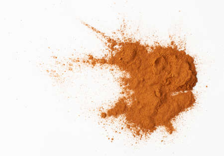 Background image of a pile of ground cinnamon on a white background. Copy space text.