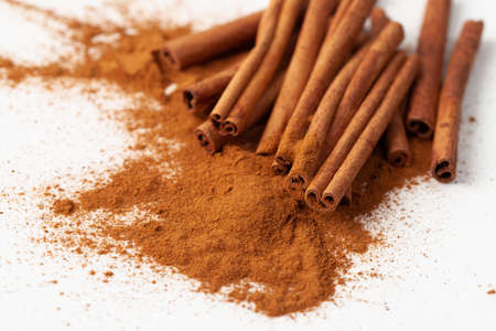 Background image a pile of ground cinnamon and cinnamon sticks on a white background for use in cooking and home made face masks