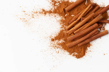 Background image of a cinnamon stick and a pile of ground cinnamon on a white background for use in cooking and medicine