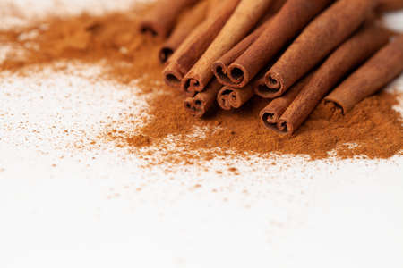 Background image macro cinnamon sticks with ground cinnamon on a white background 免版税图像