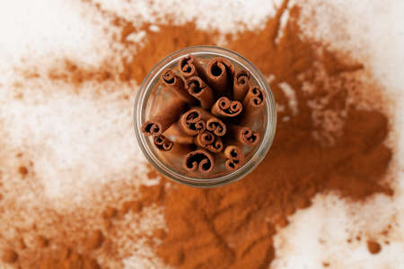 Cinnamon sticks in a glass top view on a white background in the recipes of cosmetics and cooking, folk medicine