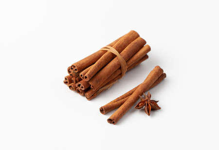 Cinnamon sticks bound and anise star on a white background in cooking and folk medicine. Copy space text.