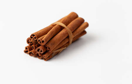 Cinnamon sticks tied on a white background in cooking and folk medicine. Copy space text.