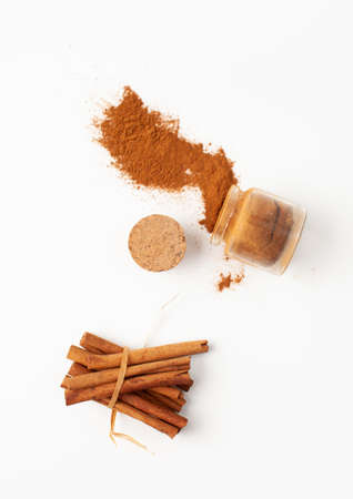 Top view of cinnamon sticks and a spilled jar of ground cinnamon on a white background in recipes cooking and folk medicine Standard-Bild