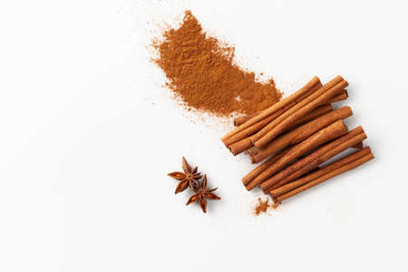 Top view of cinnamon sticks and ground cinnamon on a white background in recipes cooking and folk medicine