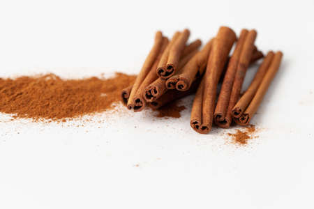 Cinnamon sticks and ground cinnamon on a white background in recipes of cooking and folk medicine. Close up. Copy space text.