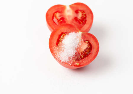 Close-up of a sliced tomato sprinkled with sugar on a white background. Tomatoes in cosmetics and folk medicine recipes on a white background. Copy space text.