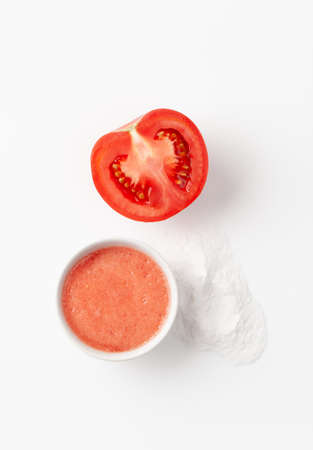 Top view organic natural recipe homemade face mask made of tomato and baking soda on a white background. Copy space text. 免版税图像