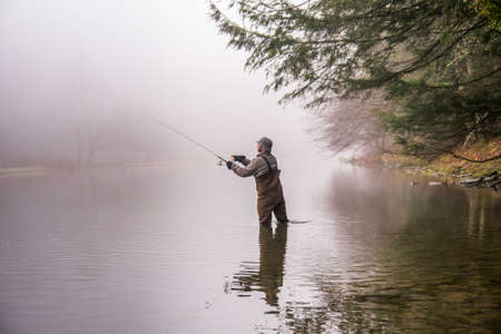 A fisherman wearing waders casts his fishing pole in a river