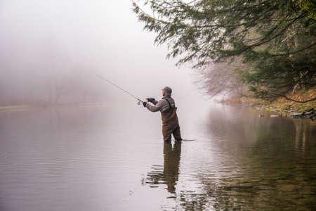 botas altas: Un pescador que llevaba botas lanza su caña de pescar en un río Foto de archivo