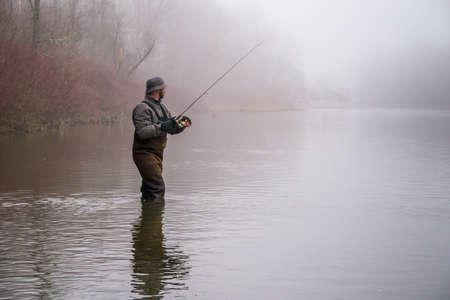 waders: A fisherman wearing waders reels in his lure