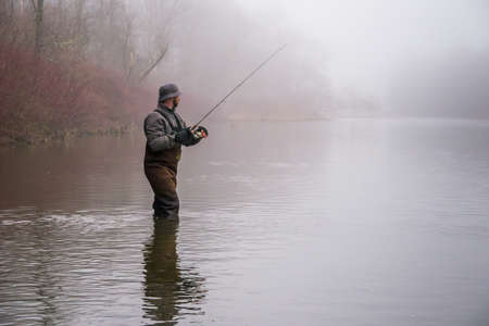 botas altas: Un pescador que llevaba botas carretes en su señuelo Foto de archivo