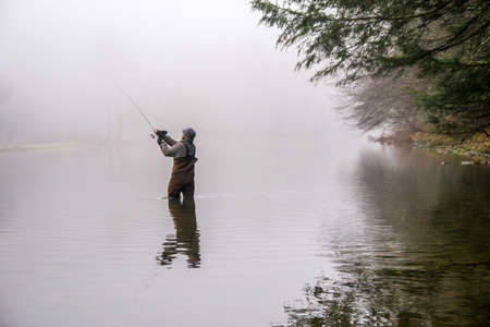 waders: a man wearing waders casts his fishing pole in a river