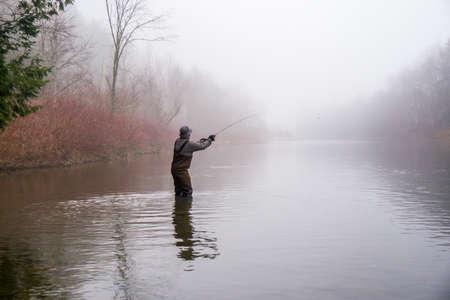 waders: un hombre que llevaba botas lanza su ca�a de pescar en un r�o