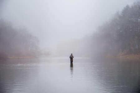 botas altas: Un pescador que llevaba botas carretes en su se�uelo Foto de archivo