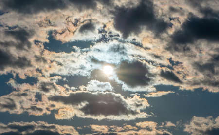 peaking: Sun peaking out behind clouds against a blue sky