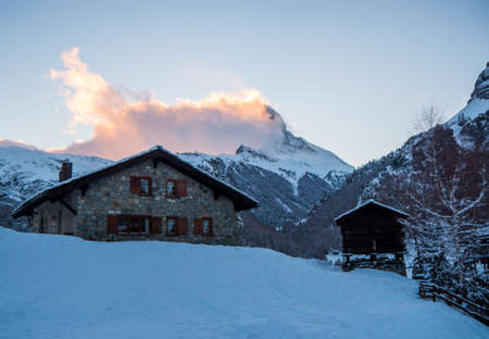 engulfed: Stone Swiss chalet with the Matterhorn in the background engulfed in clouds Stock Photo