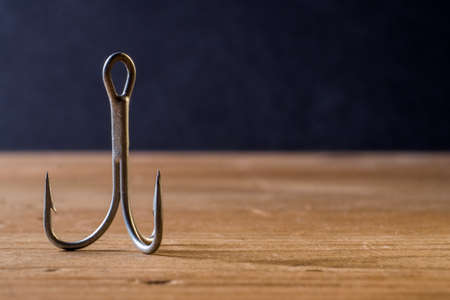 Fish Hook with 3 hooks on a wooden background