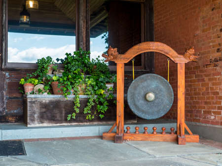 Gong with ornate wood carvings on a patio