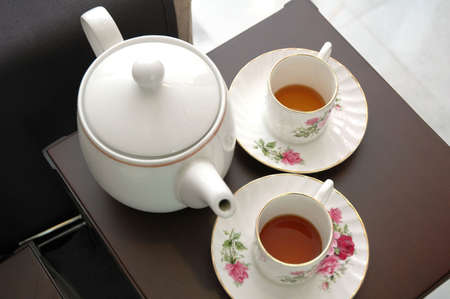 White Teacup and teapot on brown chair Stock Photo - 3843575