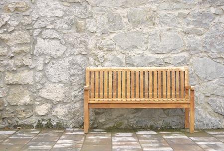 bench waiting stone wall