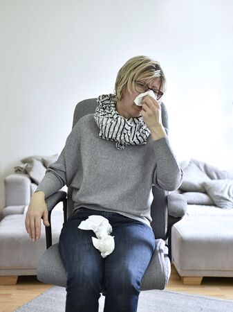 woman 40+ sick with rhinitis sitting on office chair Banque d'images