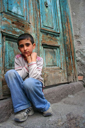A boy sitting at the doorstep and thinking photo