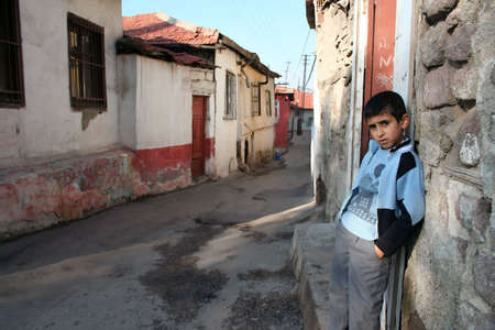 disadvantaged: A child standing in front of his house Stock Photo