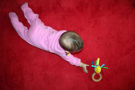 baby trying to reach her toy
