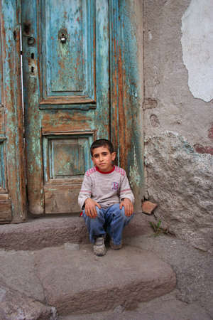 poor boy sitting in front of his house Foto de archivo