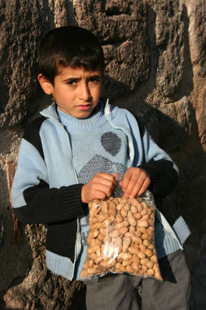 A hungry child holding his peanuts