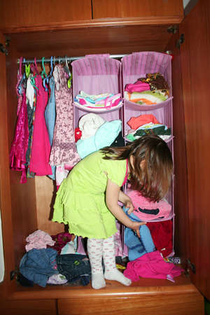 A cute child choosing dress in her wardrobe photo