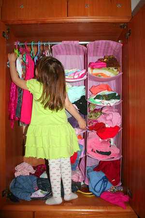 A cute child choosing dress in her wardrobe Stockfoto